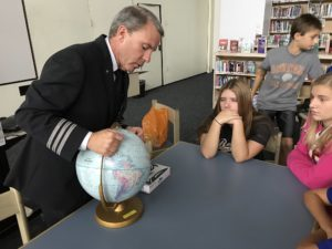 Captain Shipley demonstrating flight patterns using globe