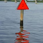 Boca Ciega Bay in Saint Petersburg Florida. A red water marker with a bird on the post