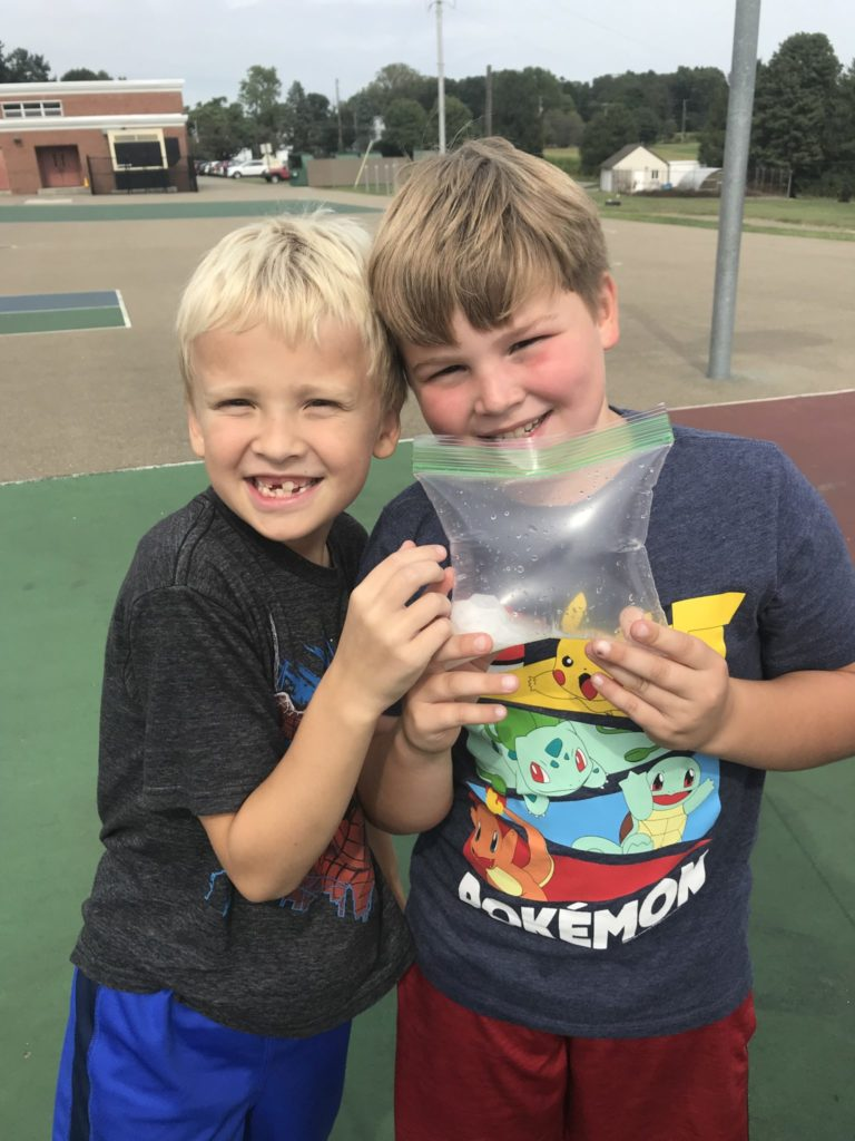 Students smiling holding plastic bag for science.