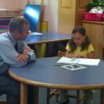 Meghan reads to Dr. Egan