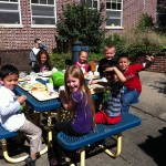 Jordan, Saurab, Victoria, Cayleigh, Aidan K., Angel, Wilfredo, and Alexis crowd around the picnic table